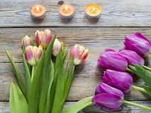 Purple tulips and candles on old wooden table. As a holiday background Stock Photo