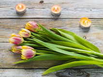 Purple tulips and candles on old wooden table. As a holiday background Royalty Free Stock Photos