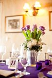 Purple tulips centerpiece at a formal dinner. Purple tulips centerpiece and purple tablecloth at a formal dinner Royalty Free Stock Photos
