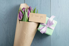 Purple tulips in craft paper on blue wood background with i love you card and gift top view. With copy space Stock Photos