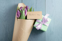 Purple tulips in craft paper on blue wood background with mothers day card and gift top view. With copy space Royalty Free Stock Photo