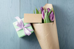Purple tulips in craft paper on blue wood background with paper card and gift top view. With copy space Royalty Free Stock Photography
