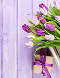 Purple tulips and gift box over wooden table Royalty Free Stock Image