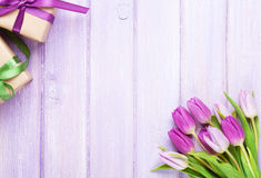 Purple tulips and gift boxes over wooden table Stock Images