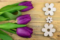 Purple tulips on old wood as background with wooden flower decoration Stock Photography