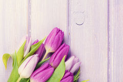 Purple tulips over wooden table Royalty Free Stock Photography