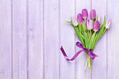Purple tulips over wooden table Royalty Free Stock Image