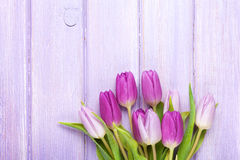 Purple tulips over wooden table Stock Images