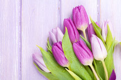 Purple tulips over wooden table Royalty Free Stock Images