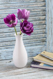 Purple tulips in a white ceramic vase and a stack of books on a blue rustic wooden background Stock Photo