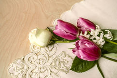 Purple tulips with white rose and hyacinth on the corner embroidered tablecloth Stock Photos