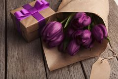 Bouqet of purple tulips and gift box on wooden background. Purple tulips on wooden background. Bouqet of violet flowers in craft paper, gift box and open book royalty free stock images