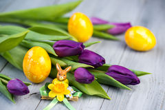 Purple tulips and yellow Easter eggs with rabbit statuette on wooden background. Purple tulips and yellow Easter eggs with rabbit statuette on grey wooden Royalty Free Stock Image