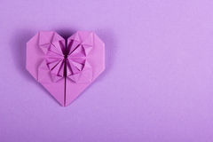 Purple Valentine origami on a lilac background. Heart of paper. Surprise on Valentine`s Day. Stock Photo