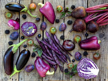 Purple vegetables and fruits on wooden background. Eggplant, peppers, beets, cauliflower, green beans, cherry tomatoes, plums, blackberries, basil, onion Stock Photos