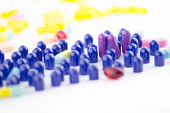 PURPLE (VIOLET) PILLS CLOSE UP. Close up of purple violet pills with blue half capsules on white background royalty free stock photography