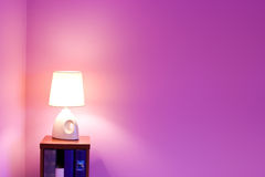 Purple wall and lamp. Purple background wall with small lamp and bookshelf royalty free stock image