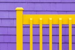 Purple wall and yellow fence. Purple shingle wall with yellow wooden fence. Decorative minimalist background in complimentary colours royalty free stock images
