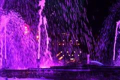 Purple water-fontain at night Stock Photos