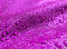 Purple waterproof fabric with waterdrops close up royalty free stock photography