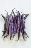Purple wax snap bean. Bunch of purple wax snap beans on white rustic board in vertical format Stock Image