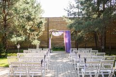 Purple wedding arch decorated with flowers, lilac and pink material. The beautiful platform for a wedding ceremony under the open. Sky: wooden white chairs, the Stock Images