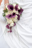 Purple wedding bouquet. Bride holding a purple wedding bouquet Royalty Free Stock Photo