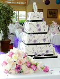 Purple wedding cake. With brides bouquet at reception Stock Photography