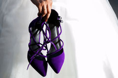 Purple Wedding Shoes. A bride holds her strappy heels by her side on her wedding day leaving her barefoot for her reception stock photos