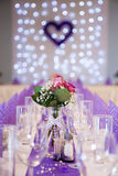 Purple wedding table decoration with focus on flower centerpiece. And glasses. Wine and water glasses are placed on a table, together with folded purple table Royalty Free Stock Photo