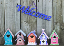 Purple welcome sign by collection of birdhouses Royalty Free Stock Photo