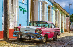 Purple and white classic American car and blue colonial building in streets of Trinidad Stock Photography