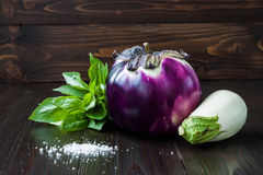 Purple and white eggplant (aubergine) with basil on dark wooden table. Fresh raw farm vegetables - harvest from the gard Stock Photos