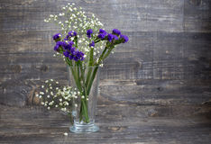 Purple and white flower bouquet in vase. On wooden background. Horizontal imagination Royalty Free Stock Image