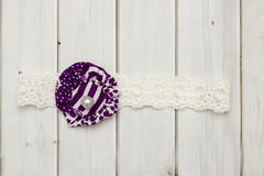 Purple and white flower headband. For newborn babies on a wooden background Royalty Free Stock Images
