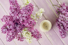 Purple and white lilac with candle on pink table Stock Image