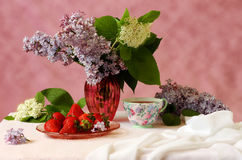Purple and white lilacs, tea and strawberries still life Royalty Free Stock Images