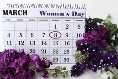 Liliums and Helichrysum flowers and calendar with marked Womens Day. royalty free stock photography