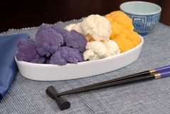 Purple, white and orange cauliflower in white serving dish. In an Asian tablescape Royalty Free Stock Photography