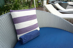 Purple and white stripe cushion on blue beach bed Stock Photos