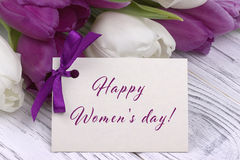 Purple and white tulips with white paper on a white wooden background and card lettering happy women`s day english. Womans Day. 8 Royalty Free Stock Photo