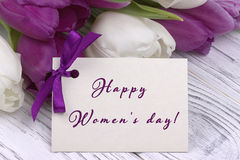 Purple and white tulips with white paper on a white wooden background and card lettering happy women`s day english. Womans Day. 8 Stock Photography