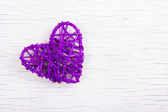 Purple wicker heart on a white wooden background. Eco Valentine. Heart of vines. Stock Photo