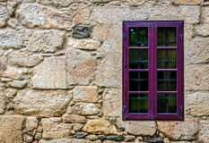 Purple window on medieval castle made of stone and rocks. Stock Photography
