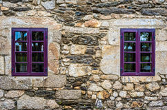 Purple window on medieval castle made of stone and rocks. Royalty Free Stock Photos