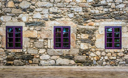 Purple window on medieval castle made of stone and rocks. Stock Photo