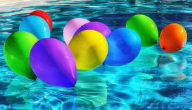 Purple Yellow and Blue Balloon on Swimming Pool Stock Photo