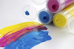Purple, yellow and blue paint in tubes. White background. Art supplies. Creative hobbies royalty free stock images