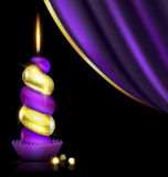 Purple yellow candle and drape. Black background, dark purple drape and the large colored burning candle Stock Images
