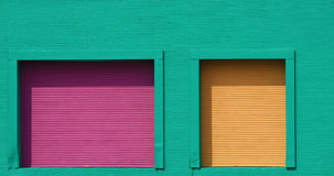Purple and Yellow Doors on Green Wall Stock Image